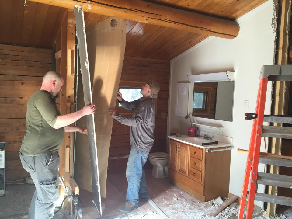 Josh at left and Gary Pohl removing the paneling covering the bathroom wall.