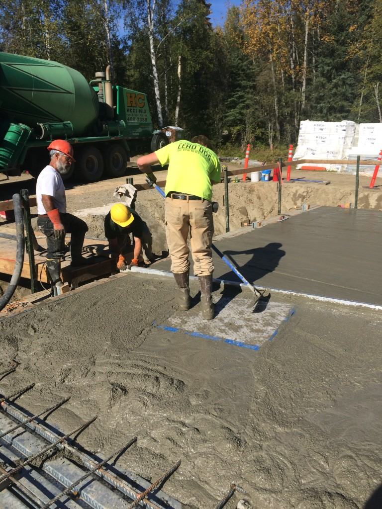 Tanner McGee screeds concrete around the access hatch.
